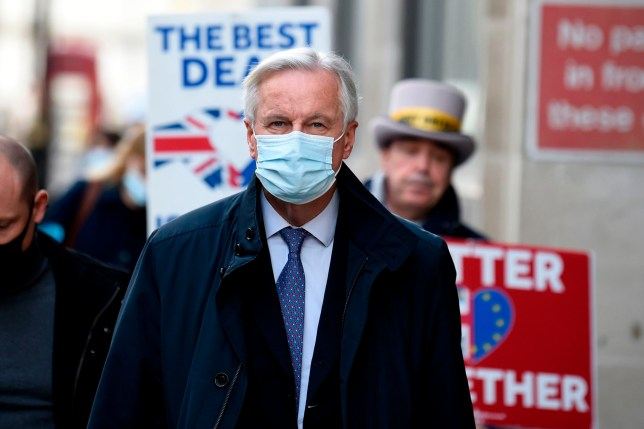 EU chief negotiator Michel Barnier wearing a face mask because of the novel coronavirus pandemic, is followed down a street by Anti-Brexit activist Steve Bray (R) as talks continue between the EU and the UK in London on November 13, 2020. - The European Union and Britain said major divergences remain but that post-Brexit negotiations would continue this week to clinch a trade deal in the scant time left. (Photo by DANIEL LEAL-OLIVAS / AFP) (Photo by DANIEL LEAL-OLIVAS/AFP via Getty Images)