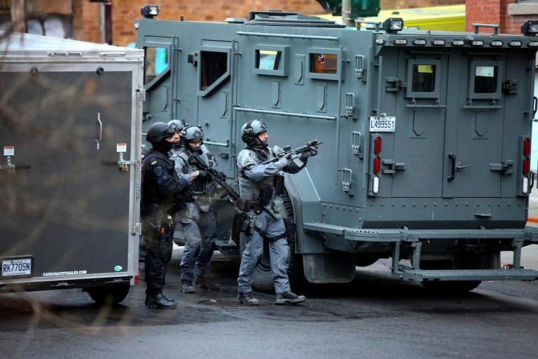 Des policiers armés avec des casques pointent une arme vers le haut derrière un véhicule blindé