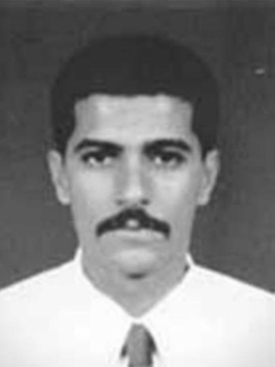 A black and white photo of a man with black hair and a moustache, a white shirt and tie
