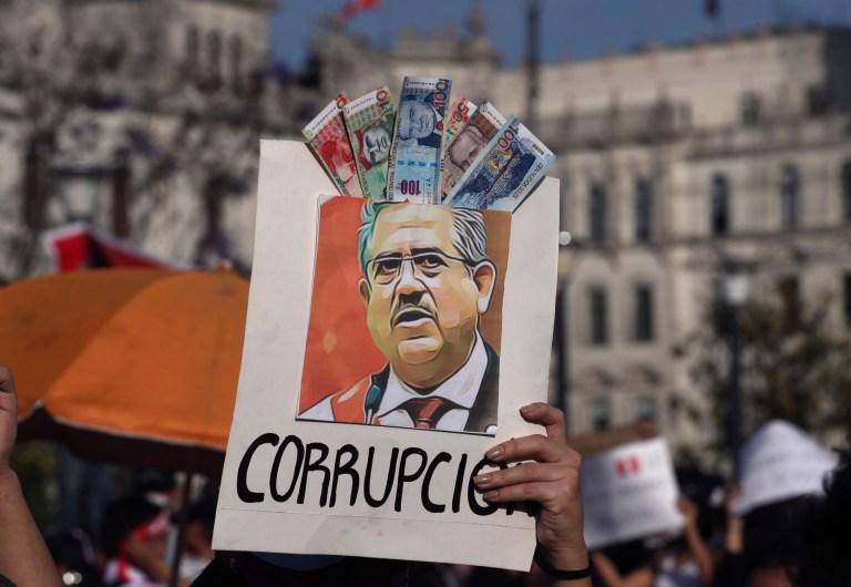 Un manifestant brandit une affiche ornée d'argent fictif avec le mot espagnol pour corruption et une image représentant le président péruvien nouvellement assermenté, Manuel Merino, sur la Plaza San Martin, où des personnes qui refusent de reconnaître le nouveau gouvernement sont rassemblées, à Lima, samedi. , 14 novembre 2020.
