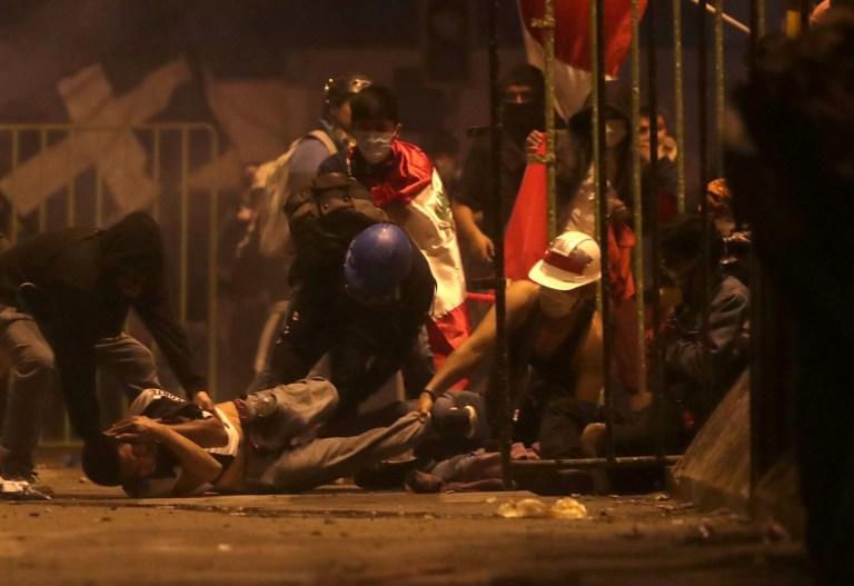 Un manifestant est blessé au sol alors qu'il est aidé par d'autres manifestants lors d'un affrontement avec la police lors d'une manifestation contre la décision du Congrès de destituer l'ancien président Martin Vizcarra, à Lima, au Pérou, le 14 novembre 2020.
