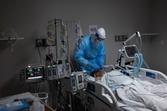 HOUSTON, TX - NOVEMBER 16: A medical staff member treats a patient suffering from coronavirus in the COVID-19 intensive care unit (ICU) at United Memorial Medical Center on November 16, 2020 in Houston, Texas. Texas has recorded more than 1.1 million cases of the disease, with more than 20,000 deaths. (Photo by Go Nakamura/Getty Images)