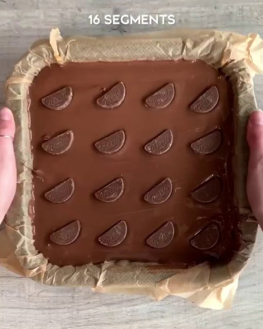 The bars in a baking tin before being cut into sections. There are Terry's Chocolate Orange segments on top of the bake.