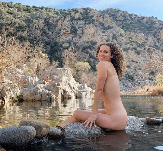 Molly sitting outside at a lake while naked