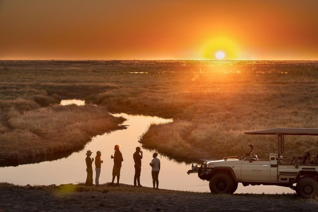 Botswana Linyati camp and expeditions. A safari jeep parked in front of a river plain at sunset.