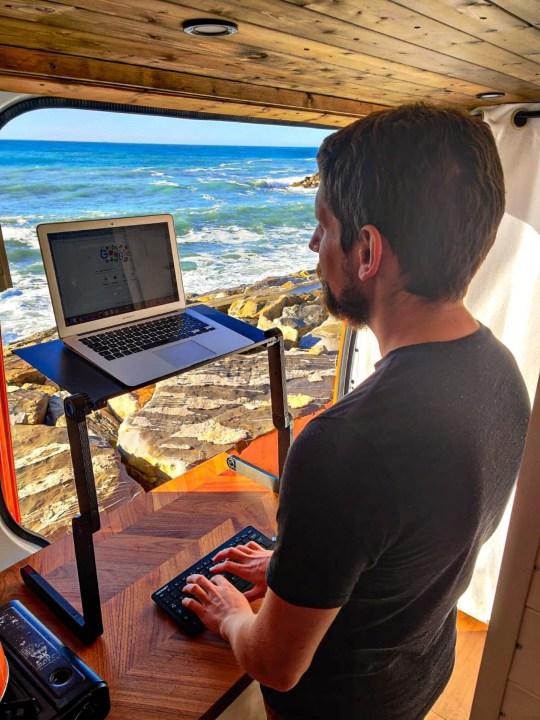 james working on a laptop in his van