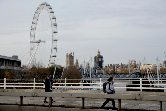 Women wear face coverings as they walk over Waterloo Bridge, backdropped by the London Eye wheel and the scaffolded Houses of Parliament and Elizabeth Tower, known as Big Ben, back centre, during England's second coronavirus lockdown, in London, Friday, Nov. 20, 2020. Britain yesterday registered 501 daily COVID-19 deaths within 28 days of a positive test and is the fifth country in the world to record more than 50,000 coronavirus-related deaths. (AP Photo/Matt Dunham)