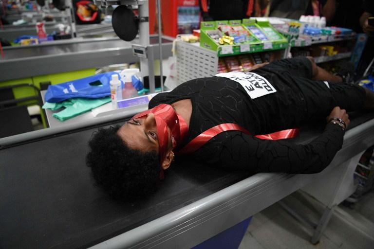 Un manifestant portant un masque rouge se trouve au-dessus d'un tapis roulant dans un supermarché