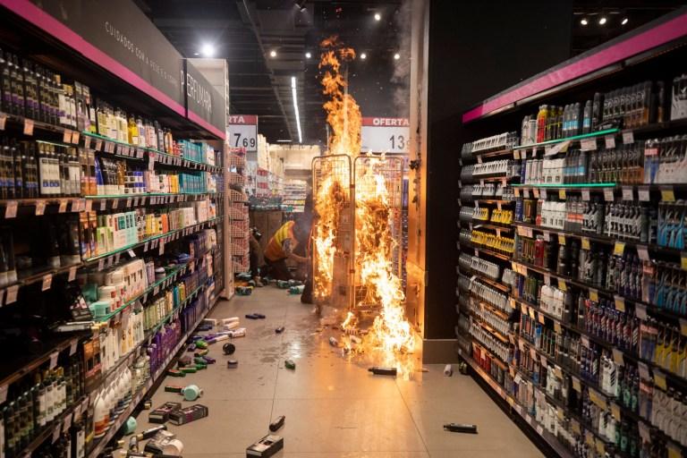 Un incendie brûle entre les allées d'un supermarché