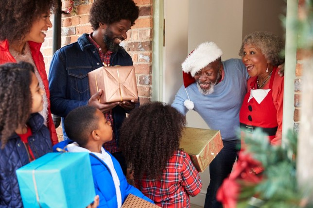 Grandparents Greeting Family As They Arrive For Visit On Christmas Day With Gifts