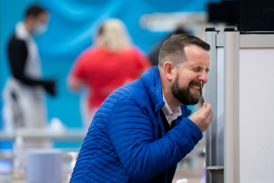 MERTHYR TYDFIL, WALES - NOVEMBER 21: A man takes a coronavirus test using a swab inserted into his nose at Merthyr Tydfil Leisure Centre on November 21, 2020 in Merthyr Tydfil, Wales. From today anybody living or working in Merthyr Tydfil will be offered a coronavirus lateral flow test in a bid to curb the spread of the virus. At the start of November, the county had the highest rate of coronavirus in the UK. While the case rate has fallen dramatically in recent weeks, it remains among the worst hit areas in Wales. (Photo by Matthew Horwood/Getty Images)