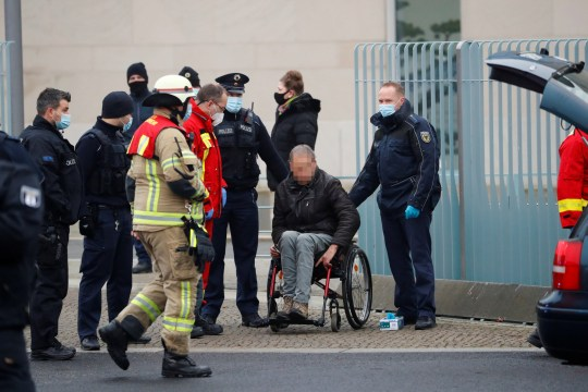 Firefighters attend a man who crashed with his car into the main gate of the chancellery in Berlin, the office of German Chancellor Angela Merkel in Berlin, Germany, November 25, 2020. REUTERS/Fabrizio Bensch