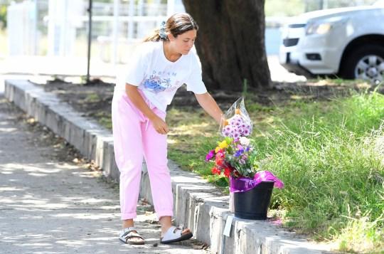 Une femme dépose des fleurs sur les lieux où un homme a été poignardé près de la gare de Seaford à Melbourne, le jeudi 26 novembre 2020