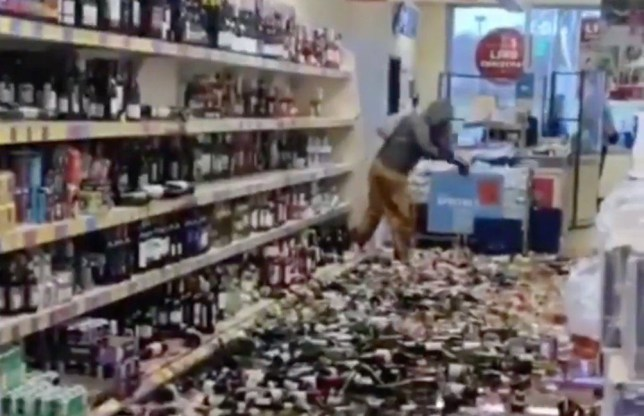 Story from Jam Press (Aldi Bottle Smash) // Pictured: A woman is seen smashing hundreds of bottles of alcohol in an Aldi store in Hertfordshire. // Shopper smashes up hundreds of booze bottles in Aldi wrecking rampage // A woman smashed hundreds of alcohol bottles on the floor of an Aldi supermarket in a wrecking rampage yesterday afternoon. In a shocking video, taken by a witness, the shopper can be seen silently dragging thousands of pounds worth of booze from the supermarket???s shelves in Hertfordshire. Another shopper queuing up at the till told the woman to ???calm down??? ??? but she retaliated and tossed a bottle of gin at his leg, according to reports. The woman, who was wearing a hoodie, backpack and mustard trousers ended up slipping on the mess and cut her right hand, it has also been reported. In the clip, the aggravated shopper is seen raising one hand in the air as she continues breaking several bottles on the floor. She was later arrested by police at around 2.30pm, after a security guard managed to detain the suspect and dragged her out of the shop. ???Police were called at around 2.30 pm on Wednesday to report an incident at the Aldi supermarket in Fairlands Way, Stevenage,