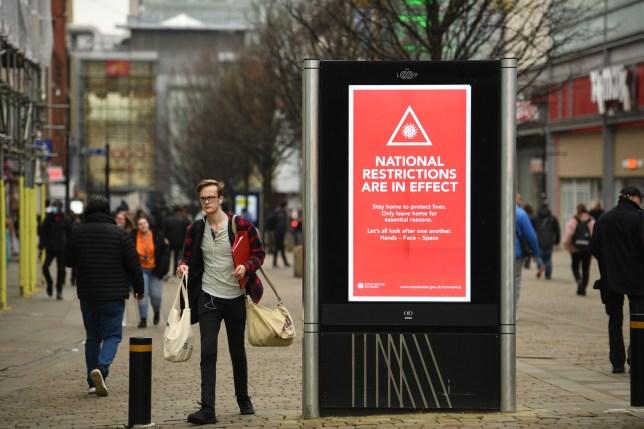 Les piétons marchent devant un panneau affichant un message du conseil municipal de Manchester sur les restrictions de verrouillage national