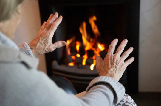 Elderly person warming their hands on a fire