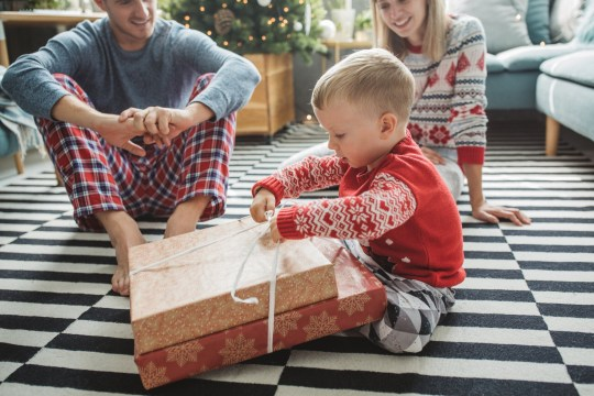 Young parents with baby boy celebrating Christmas at home, boy opening presents . Home is decorated with Christmas ornaments and lights.