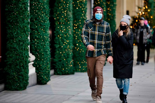 Pedestrians wearing a masks because of the novel coronavirus pandemic walk past a store front covered in Christmas decorations in central London on November 20, 2020, as life under a second lockdown continues in England. - The current lockdown in England has shuttered restaurants, gyms and non-essential shops and services until December 2, with hopes business could resume in time for Christmas. (Photo by Tolga Akmen / AFP) (Photo by TOLGA AKMEN/AFP via Getty Images)