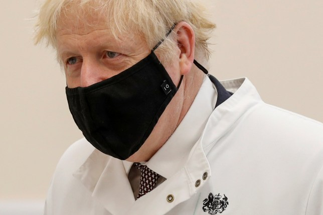 FILE PHOTO: Britain's Prime Minister Boris Johnson wears a face mask as he visits the Public Health England site at the Porton Down science park, near Salisbury, Britain November 27, 2020. Adrian Dennis/Pool via REUTERS/File Photo