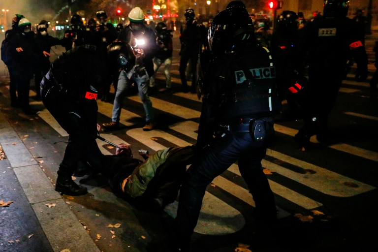 A demonstrator is arrested and draged on the ground by a group of French anti-riot police during a demostration in Paris