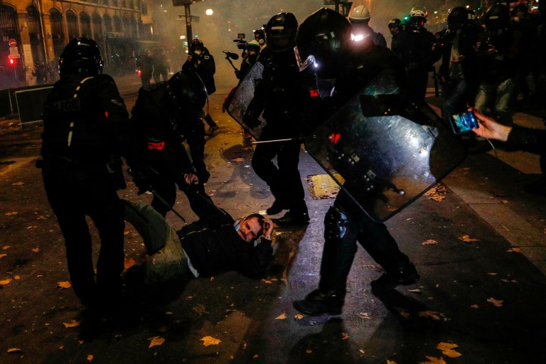 A person films a demonstrator as he is arrested and dragged on the ground by a group of French anti-riot police
