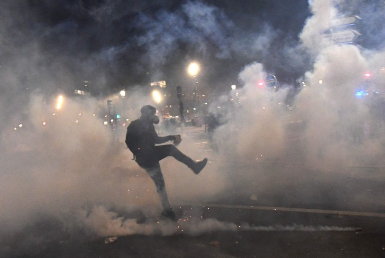 A demonstrator reacts during clashes with French riot police in a protest against the 'global security' draft law