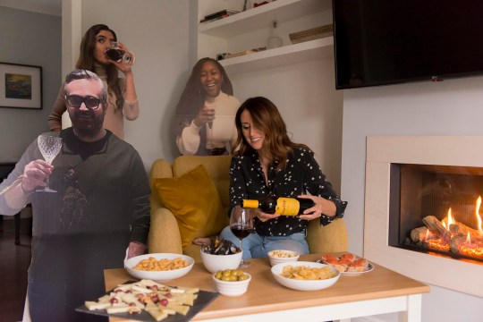 a woman drinking alone surrounded by cardboard cutouts of people