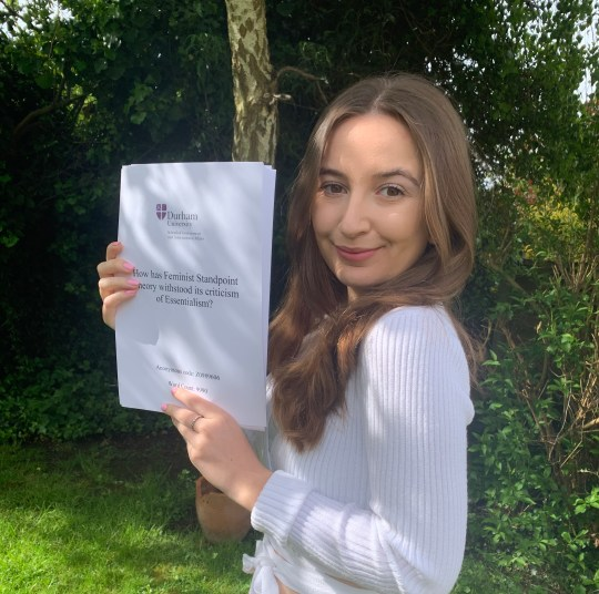 Darcey Sergison holding her dissertation