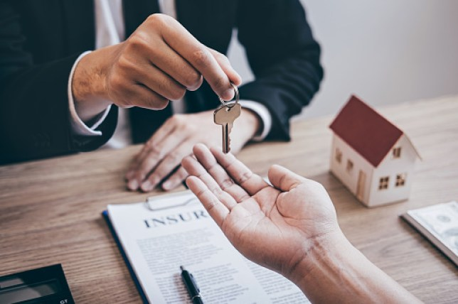 Midsection Of Agent Giving Key To Customer In Office after buying property with stamp duty holiday/