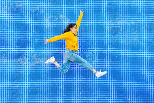 Woman jumping in front of a blue background