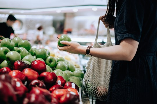 Woman shopping for apples in a supermarket