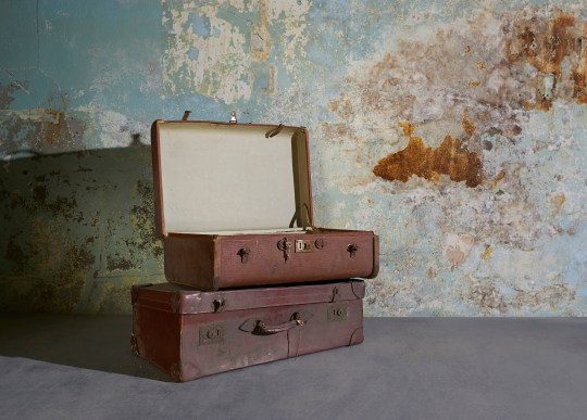 Vintage suitcases in room with decaying wall