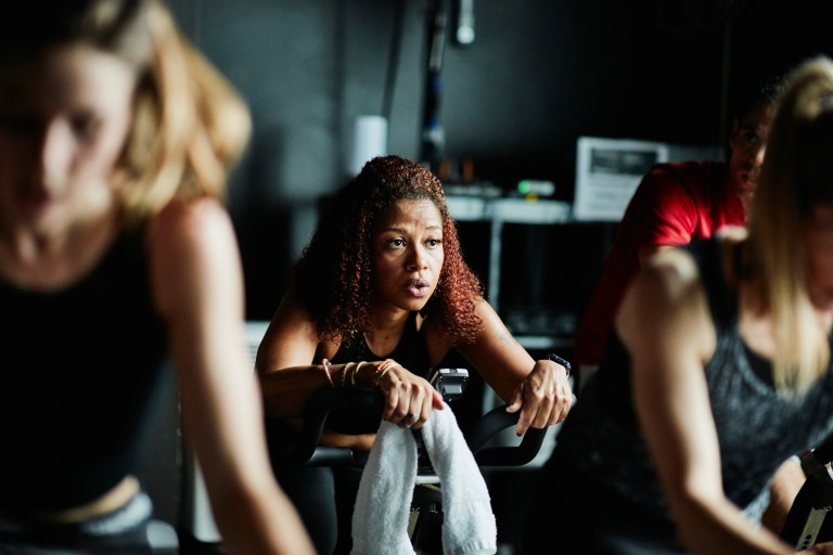 Exhausted woman on stationary bike in fitness studio after cycling class
