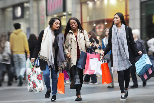 Three young women in town shopping