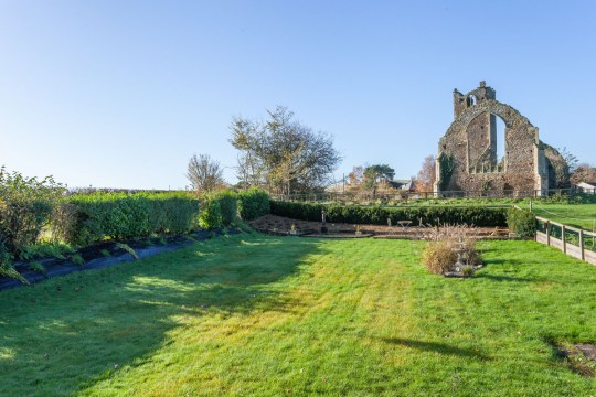 former lodge house up for sale in norwich, garden view of church ruins