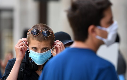 epa08560343 A customer is handed a face mask to wear inside a store on Oxford Street in London, Britain, 22 July 2020. The British government has announced it is mandatory to wear face masks in shops from 24 July on, to help mitigate the spread of coronavirus. EPA/ANDY RAIN