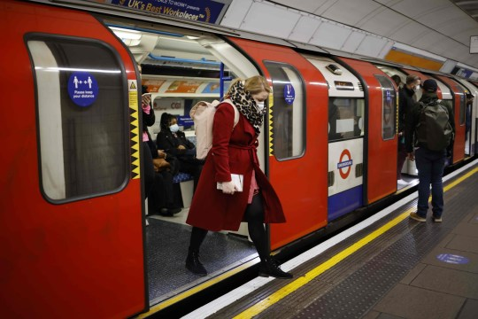 Passengers, wearing masks because of the coronavirus pandemic, exit a London Underground tube train during the morning rush hour in London on December 2, 2020 as England emerges from a month-long lockdown to combat the spread of Covid-19. - England on December 2 exited a month-long lockdown into a new 3-tiered system of curbs with non-essential retail, leisure centres and salons all reopening but with some sectors, including hospitality, seeing tighter restrictions. (Photo by Tolga Akmen / AFP) (Photo by TOLGA AKMEN/AFP via Getty Images)