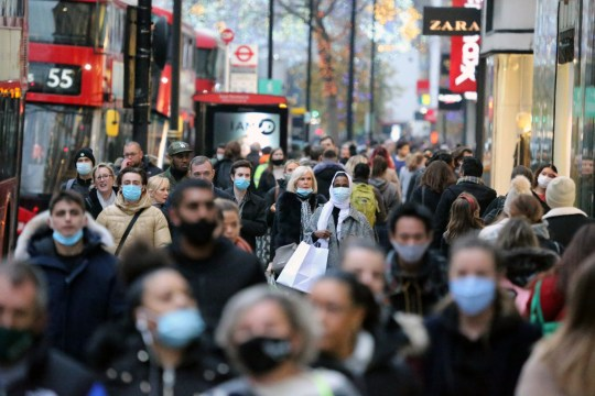 LONDON, UNITED KINGDOM - DECEMBER 2: People walk at Oxford street as all non-essential shops open after national lockdown imposed to curb the spread of the coronavirus (Covid-19), formally lifted due to upcoming Christmas in London, United Kingdom on December 2, 2020. Four weeks nationwide lockdown ended today and new tier system entered into force in the country easing restrictions on travel and shopping. (Photo by Tayfun Salci/Anadolu Agency via Getty Images)