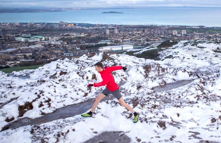 A fell runner runs through the snow on the summit of Arthur's Seat in Holyrood Park, Edinburgh