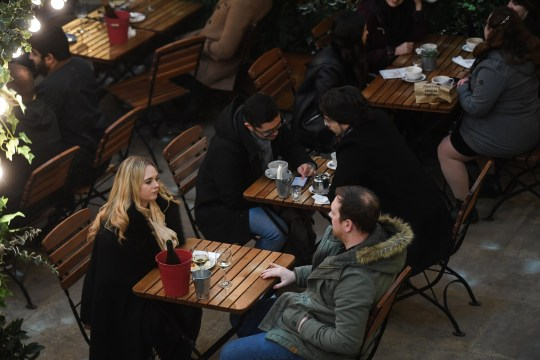 People sit outside a pub in Covent Garden on December 5, 2020 in London, England.