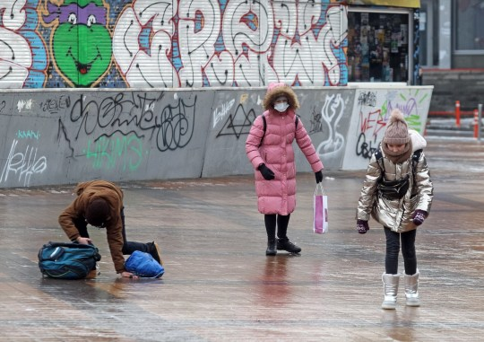 Crédit obligatoire: Photo de Pavlo Gonchar / SOPA Images / REX (11538981h) Un garçon est tombé en marchant sur un trottoir glissant après une forte pluie.  Kiev a été paralysée en raison de la détérioration des conditions météorologiques après des chutes de pluie verglaçante.En conséquence, les trottoirs et les routes ont été gelés, des embouteillages importants se sont formés et une augmentation significative des blessures de piétons et de nombreux accidents de la circulation se sont produits.  La pluie gelée a paralysé Kiev, Ukraine - 11 décembre 2020
