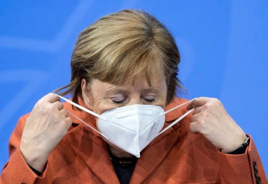Après la conférence de commutation entre elle et les premiers ministres des États fédéraux, la chancelière Angela Merkel (CDU) ajuste son masque et commente la suite de la crise de Corona lors d'une conférence de presse à la chancellerie fédérale, le dimanche 13 décembre, 2020. (Bernd von Jutrczenka / dpa via AP)