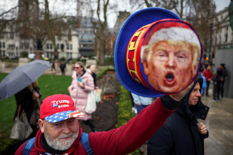 An anti-vaccination activist wearing a Trump support campaign cap attends a demonstration at the Parliament Square in London, Britain, December 14, 2020.