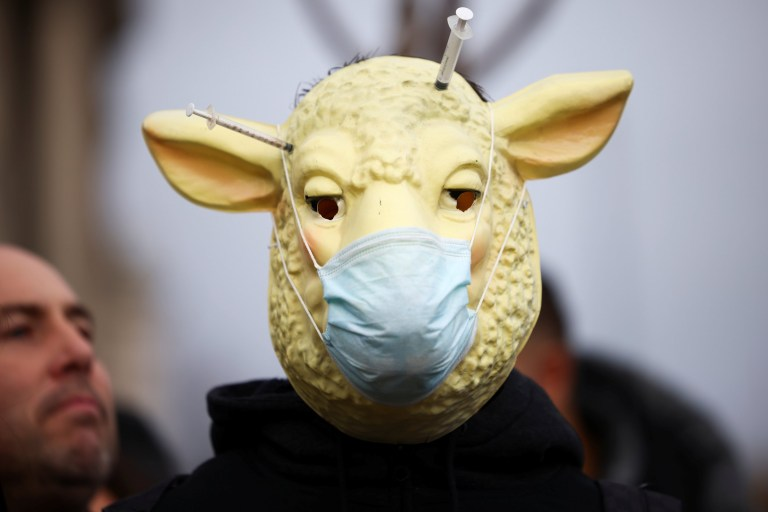 A person with a lamb mask participates in an anti-vaccination demonstration at the Parliament Square in London, Britain, December 14, 2020.