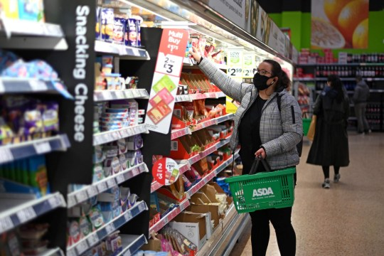 A shopper wearing a protective face covering to combat the spread of the coronavirus, chooses items off the shelves of an Asda supermarket in London on December 14, 2020. - With just over two weeks to go until Britain leaves the EU single market, preparations have been stepped up as fears grow about the impact of customs checks and congested ports. Concern is rising over the supply of perishable fresh fruit and vegetables, much of which is imported from EU countries. (Photo by DANIEL LEAL-OLIVAS / AFP) (Photo by DANIEL LEAL-OLIVAS/AFP via Getty Images)