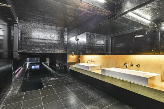 a dark brutalist bathroom with a narrow pool off to the side