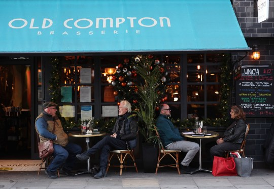 People drinking on outdoor tables at Old Compton Brasserie in Soho, London.