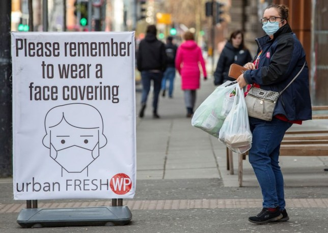 A pedestrian wearing a face covering walks past a COVID-19 information sign in Belfast on November 27, 2020, as stricter rest