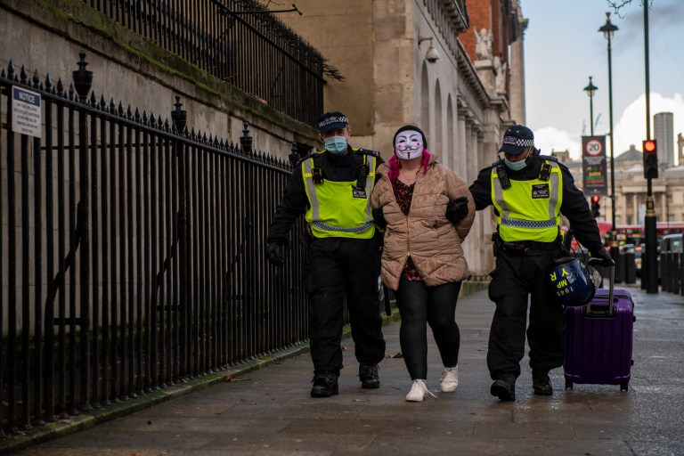 LONDON, ENGLAND - DECEMBER 19: A woman wearing a face mask is arrested during an anti lockdown protest on December 19, 2020 in London, England. With the majority of the United Kingdom now under the strictest tier 3 lockdown, Prime Minister Boris Johnson is due to hold a press conference later in the day to update the public on advice around travel and gatherings at Christmas. (Photo by Chris J Ratcliffe/Getty Images)