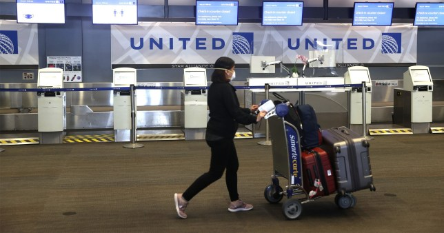 SAN FRANCISCO, CALIFORNIA - JULY 08: A United Airlines passenger pushes a luggage cart past closed check-in kiosks at San Francisco International Airport on July 08, 2020 in San Francisco, California. As the coronavirus COVID-19 pandemic continues, United Airlines has sent layoff warnings to 36,000 of its front line employees to give them a 60 day notice that furloughs or pay cuts could occur after October 1. (Photo by Justin Sullivan/Getty Images)